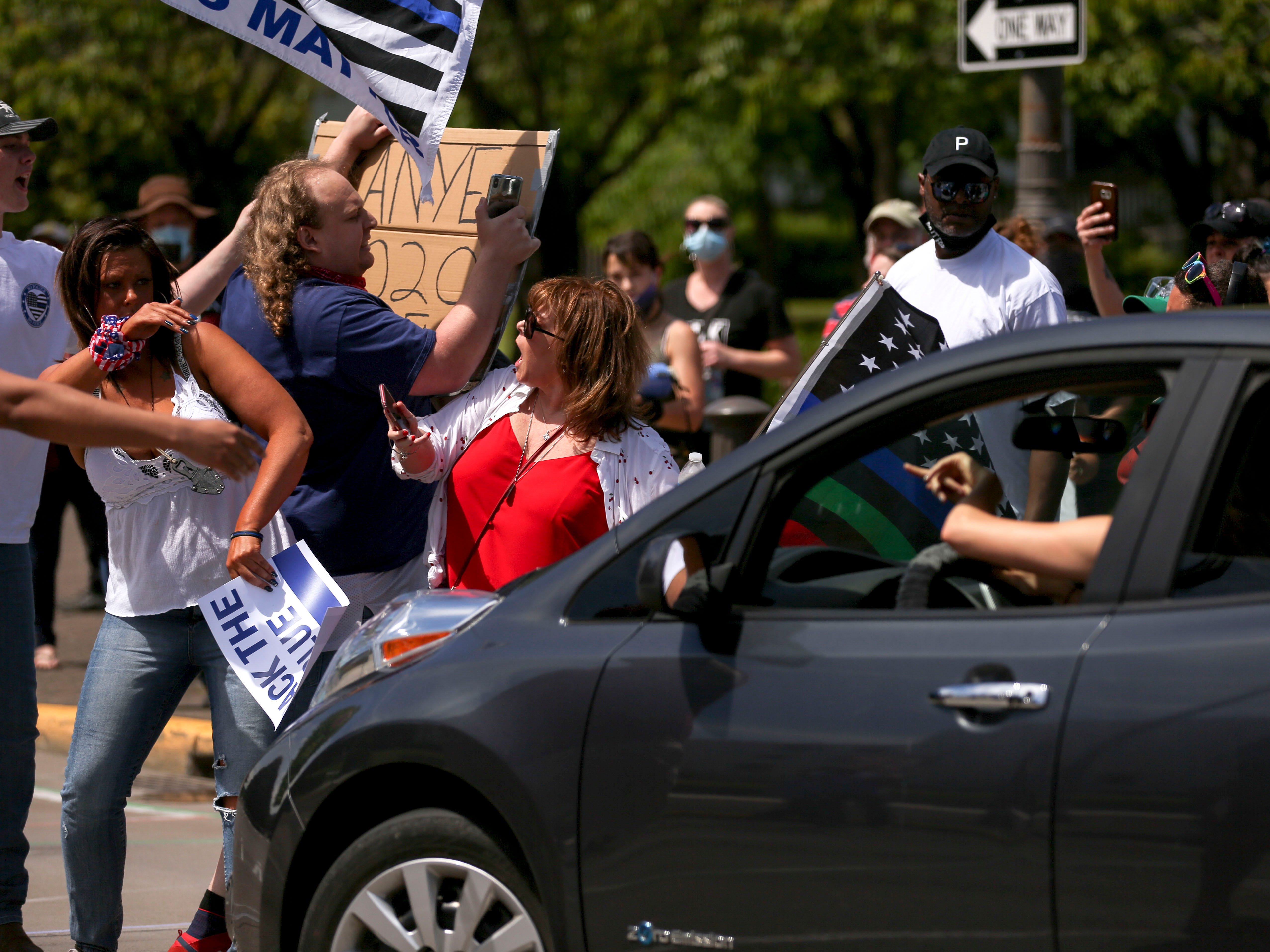 """Pro-police and anti-police violence demonstrators work together to remove a person blocking traffic while holding a """"Kanye 2020"""" sign during multiple rallies at the Oregon State Capitol, in Salem, Oregon, on Saturday, July 11, 2020."""