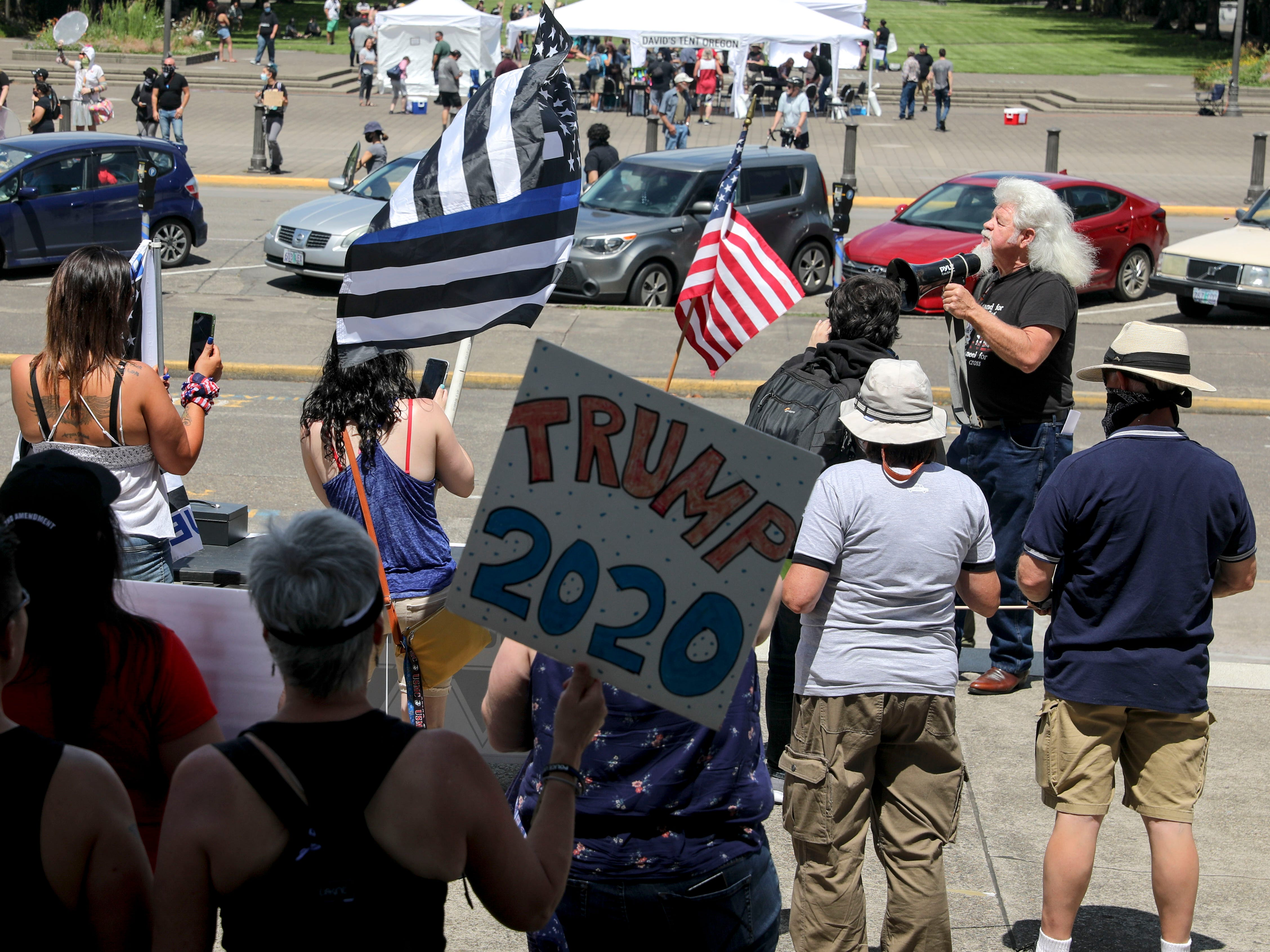 Demonstrators watch as Jim Cropper sings during the Back the Blue rally at the Oregon State Capitol, in Salem, Oregon, on Saturday, July 11, 2020.